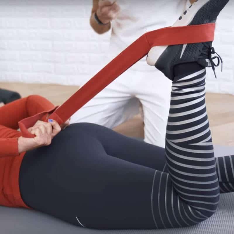 Für eine Oberschenkel-Übung gegen Knieschmerzen zieht eine Patientin auf der Matte liegend ihren Fuß mit der Liebscher & Bracht-Übungsschlaufe in Richtung Gesäß