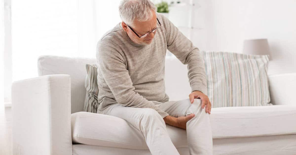 Mann sitzt auf einem Sofa und fasst sich in die Kniekehle bei Schmerzen mit einer Bakerzyste.