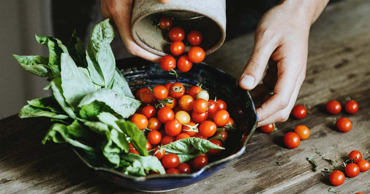 Ein großer Teller voll mit Grünzeug und Tomaten