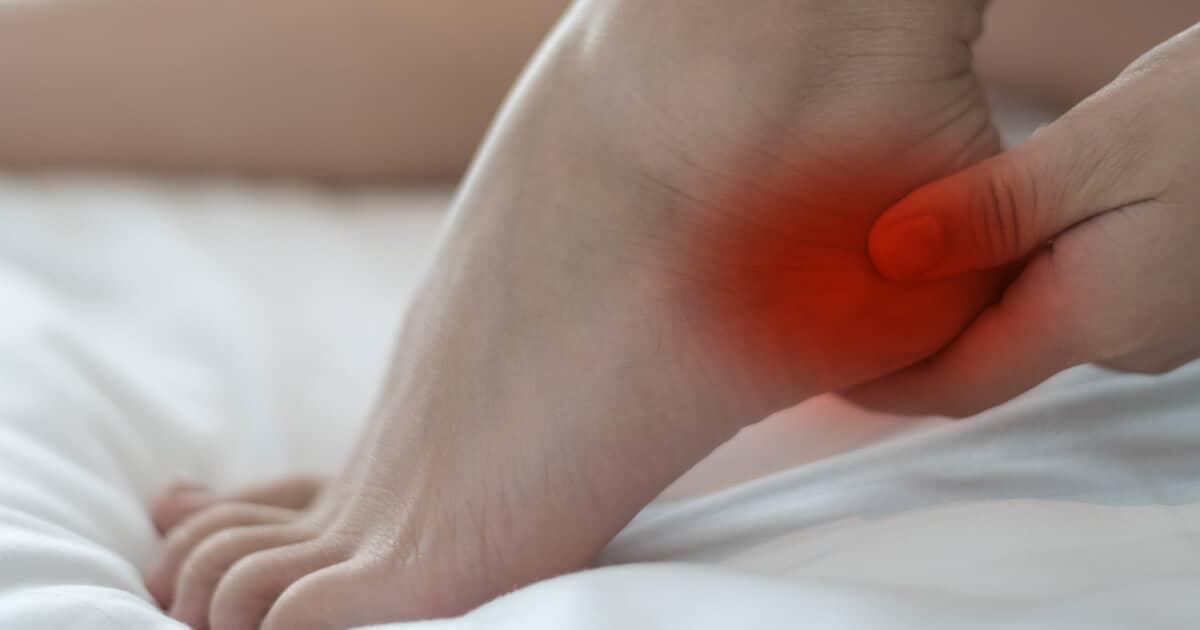Zu sehen ist ein Fuß und eine Hand, die an die schmerzhafte Ferse fasst.