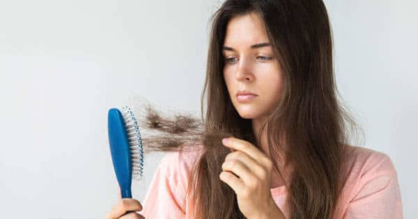 Frau rupft lose Haare aus der Bürste