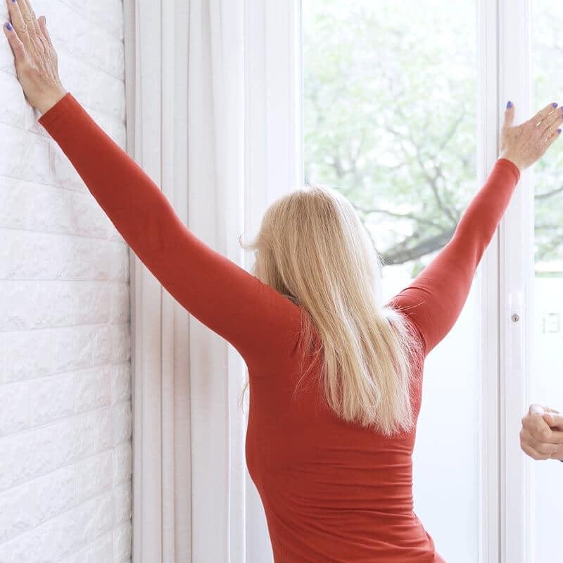 Eine Frau macht eine Dehnübung gegen Schulterschmerzen und hat dabei Schmerzen beim Dehnen. Sie steht in einer freien Raumecke und stützt sich mit ihren Händen an der Wand ab.