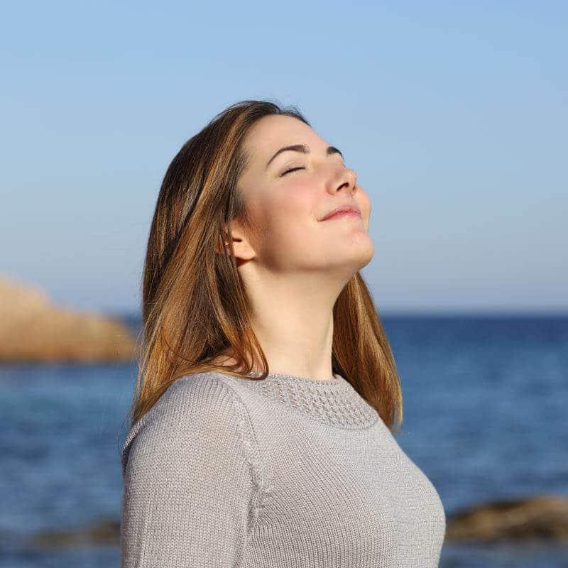 Eine Frau steht am Meer, hat ihren Kopf gen Sonne und Himmel gewandt und atmet tief ein
