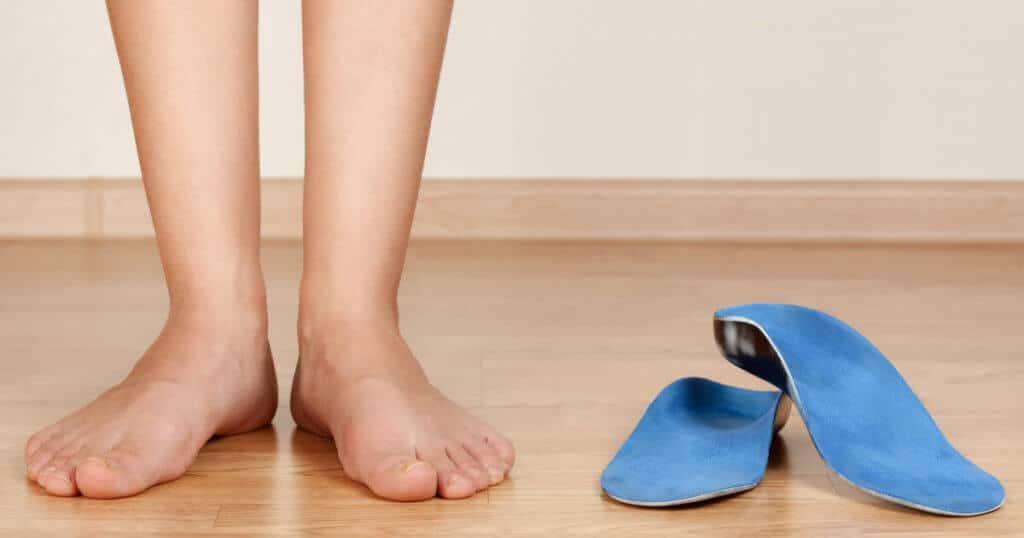 Füße neben blauen Einlegesohlen