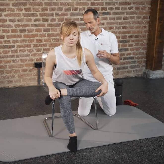 Frau mit Piriformis-Syndrom macht Übungen gegen ihre Gesäß-Schmerzen. Sie sitzt auf einem Stuhl und ihr linker Knöchel liegt auf ihrem rechten Knie.