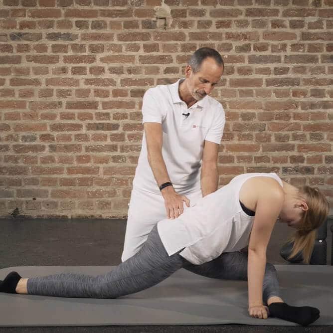 Frau mit Piriformis-Syndrom macht eine Übung mit Gesäß-Schmerzen. Sie befindet sich in einer Grätsch-Haltung und hebt ihr Gesäß an.