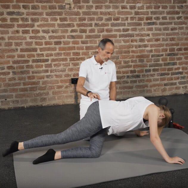 Frau im Vierfüßler-Stand macht eine Übung gegen das Piriformis-Syndrom. Sie kniet auf dem Boden und hebt ihr rechtes Bein an.
