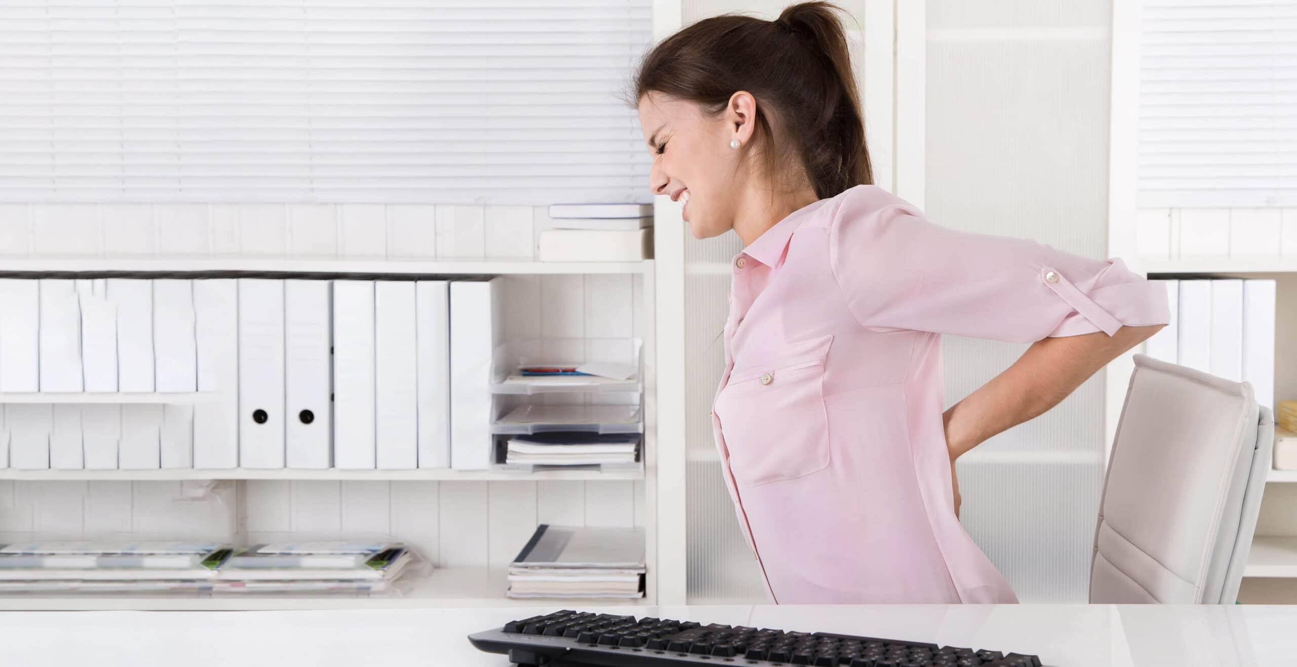 Eine Frau sitzt am Schreibtisch und stuetzt sich wegen ihrer Schmerzen den unteren Ruecken.