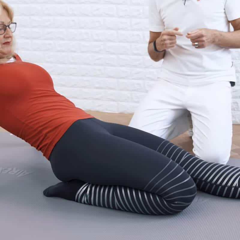 Eine Frau kniet auf einer Matte und macht eine Dehnübung gegen Knieschmerzen