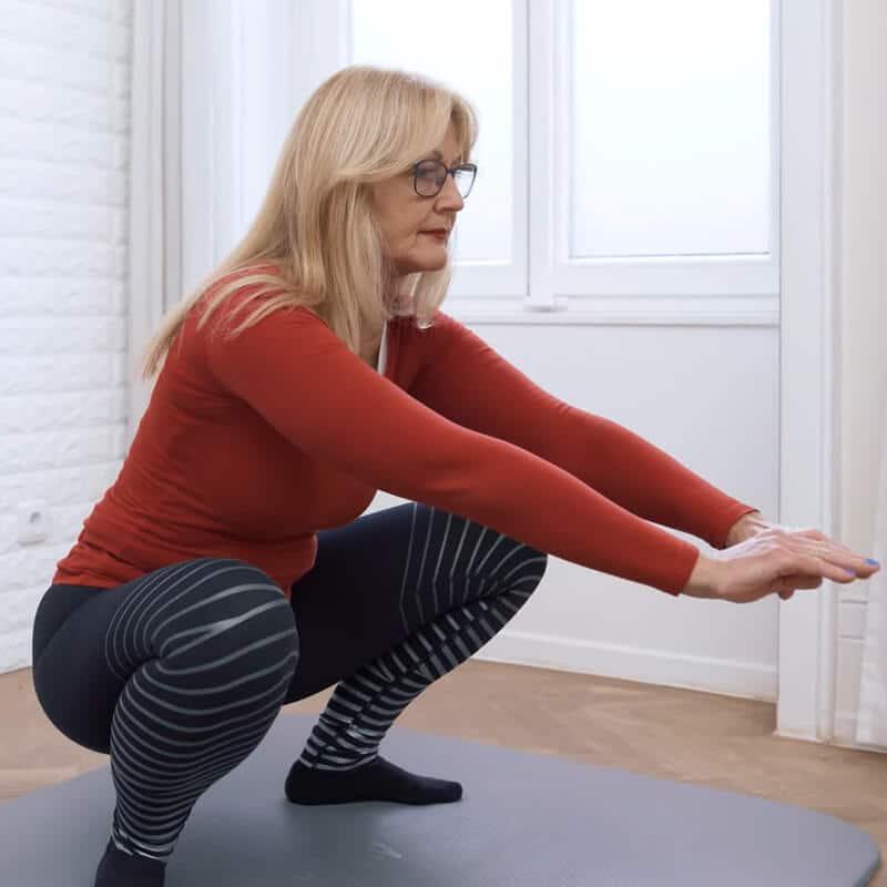 Eine Frau macht in langsamer Geschwindigkeit Kniebeugen, um ihre Knieschmerzen loszuwerden