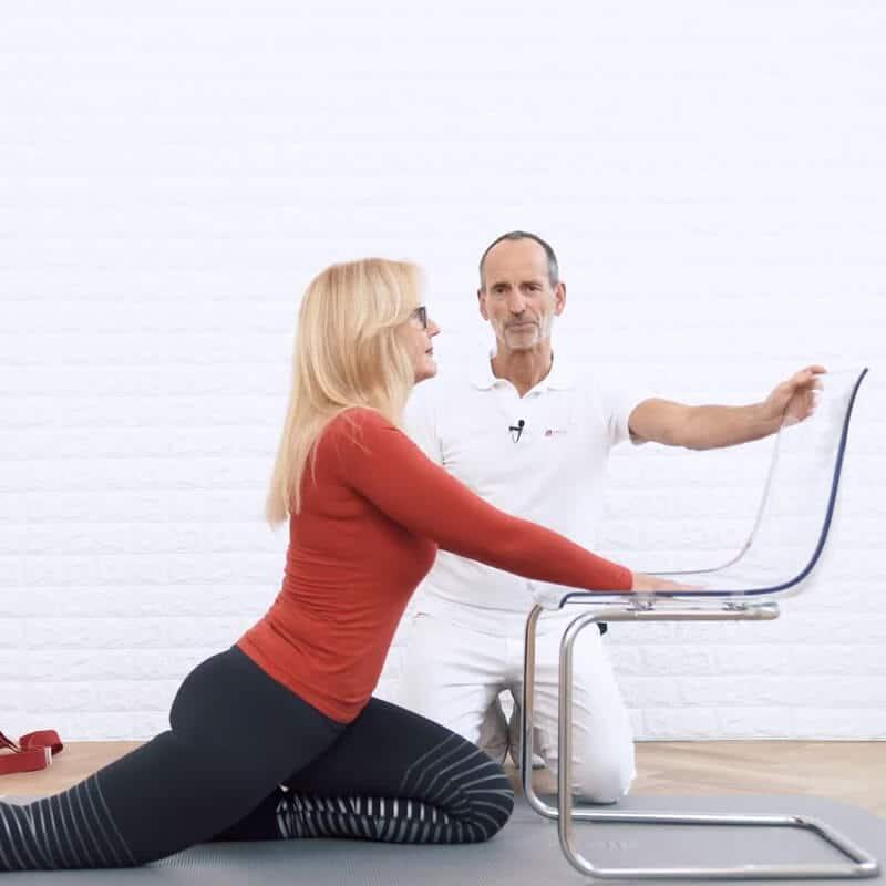 Schmerzspezialist Roland Liebscher-Bracht zeigt einer Patientin eine Spezial-Übung gegen Rückenschmerzen. Sie liegt auf einer Matte, die linke Gesäßhälfte ist auf der linken Ferse abgelegt, während das rechte Bein nach hinten durchgestreckt ist. Die Abstützung erfolgt auf einem Stuhl.