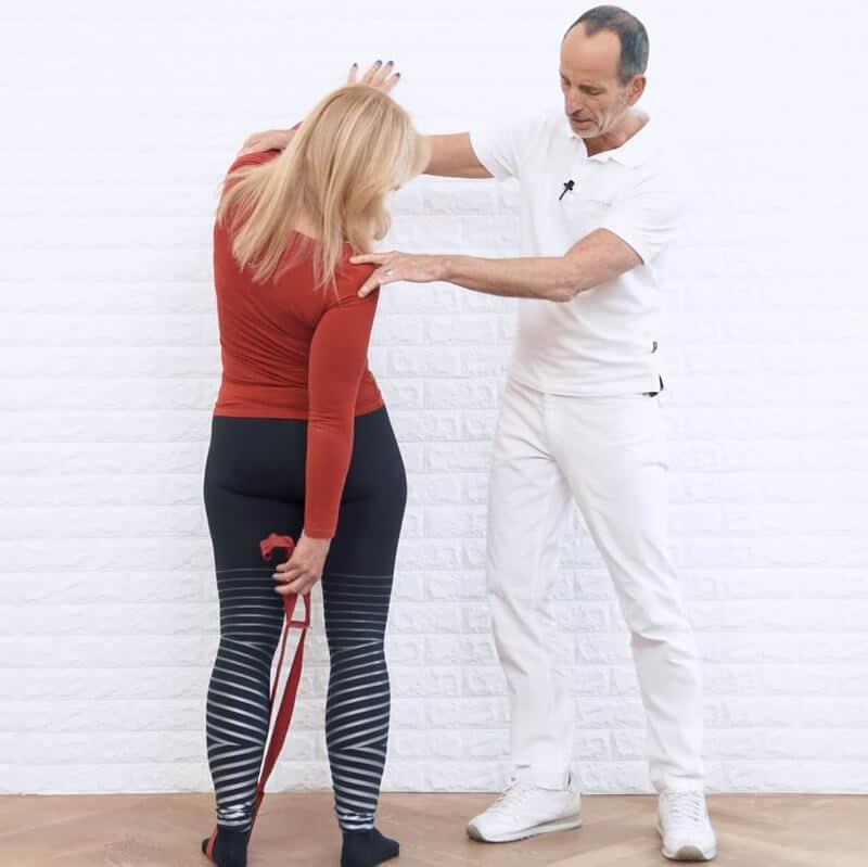 Schmerzspezialist Roland Liebscher-Bracht zeigt einer Patientin eine Spezial-Übung gegen Rückenschmerzen. Sie steht hüftbreit frontal vor einer Wand und stützt sich mit der linken Hand an der Wand ab. Der linke Fuß liegt in der Übungs-Schlaufe. Mit der rechten Hand greift die Patientin die Schlaufe, wobei sie sich nach rechts in die Drehung begibt.