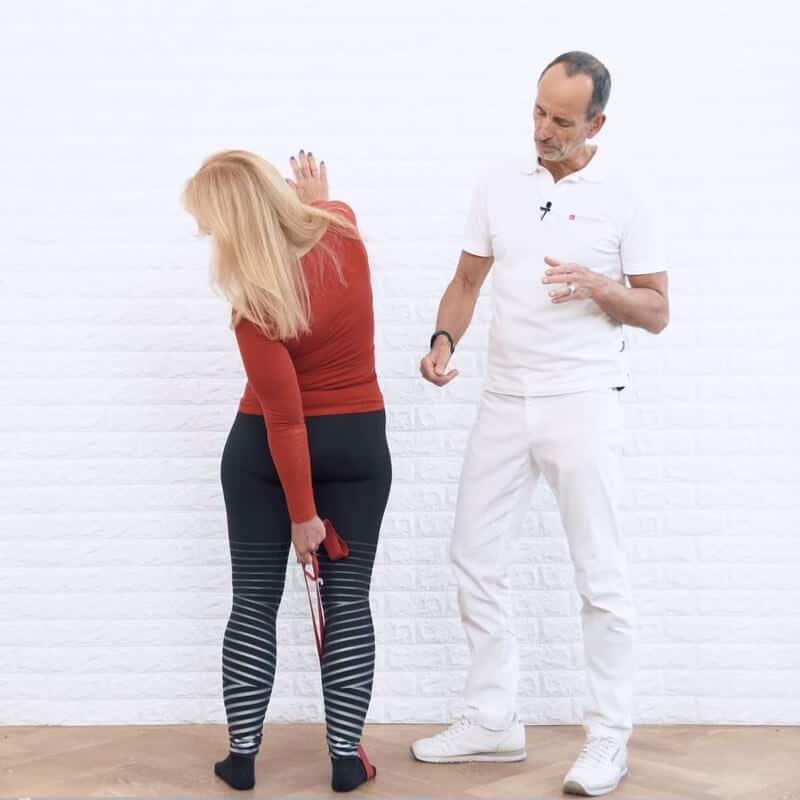 chmerzspezialist Roland Liebscher-Bracht zeigt einer Patientin eine Spezial-Übung gegen Rückenschmerzen. Sie steht hüftbreit frontal vor einer Wand und stützt sich mit der rechten Hand an der Wand ab. Der recht Fuß liegt in der Übungs-Schlaufe. Mit der linken Hand greift die Patientin die Schlaufe, wobei sie sich nach links in die Drehung begibt.