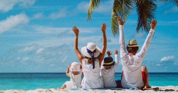 Eine Familie sitzt am Strand und freut sich