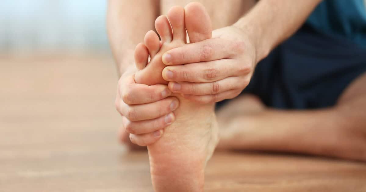 Mann hält sich vor Schmerzen die Fußsohle aufgrund einer Thrombose