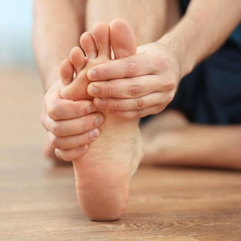 Mann hält sich vor Schmerzen die Fußsohle bei einer Plantarfasziitis
