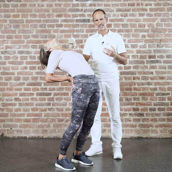 Eine Frau macht eine Übung gegen ihre Bandscheibenschmerzen und beugt sich mit ihrem Körper nach hinten