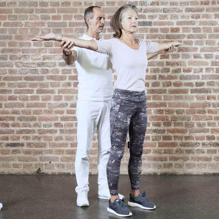 Frau macht eine Übung gegen schmerzende Bandscheiben, ihre Arme sind auf Schulterhöhe ausgebreitet