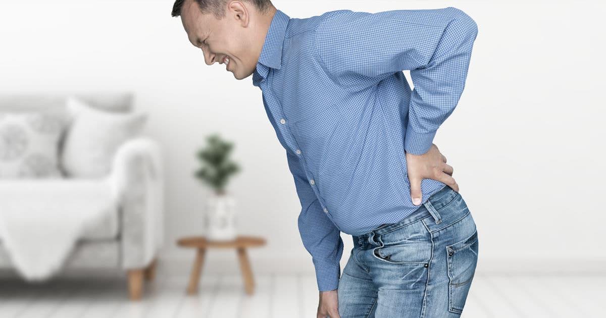 Mann, der sich vor Schmerzen den Rücken mit der Hand festhält und ein schmerzverzerrtes Gesicht macht
