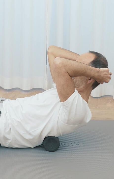 Roland Liebscher-Bracht führt die Faszien-Rollmassage am Schambein aus