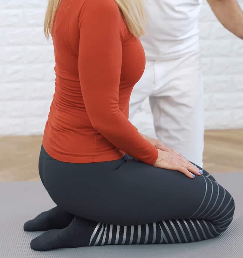 Eine Frau sitzt auf einer Matte im Fersensitz