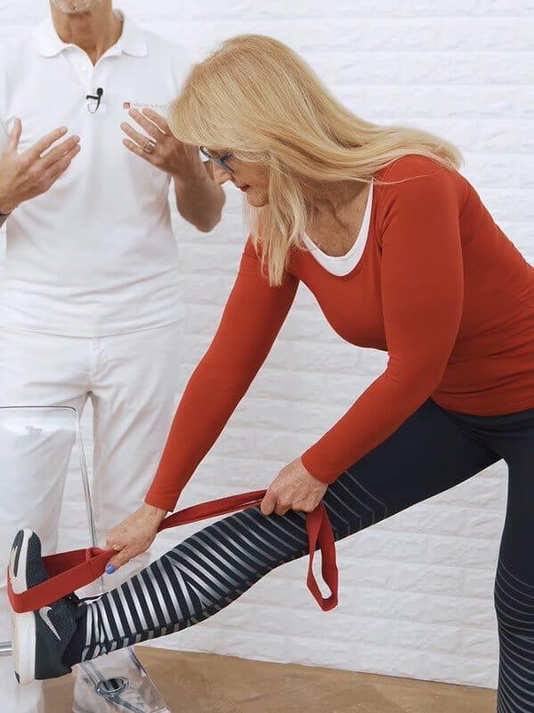 Eine Frau zieht mithilfe der Übung-Schlaufe von Liebscher & Bracht ihr Bein näher zu sich ran.