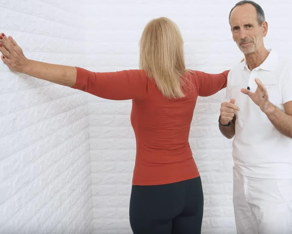 Eine Patientin führt den 3-Minuten-Trick gegen Brustschmerzen aus. Sie steht vor einer Ecke im Raum und spreizt die Arme seitlich weg, um sich in die Ecke hineinfallen zu lassen, indem sie sich an den Wänden abstützt.
