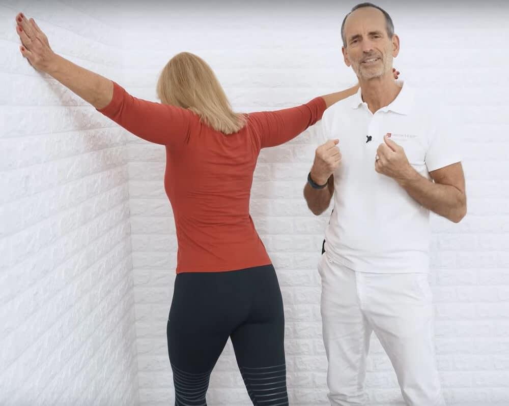 Eine Patientin führt den 3-Minuten-Trick gegen Brustschmerzen aus. Sie steht vor einer Ecke im Raum und spreizt die Arme seitlich weg, um sich in die Ecke hineinfallen zu lassen, indem sie sich an den Wänden abstützt. Ihre Beine befinden sich in Schrittstellung