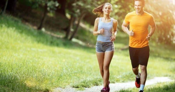 Eine Frau und ein Mann joggen durch einen Park. Sie laecheln und sehen fit aus.