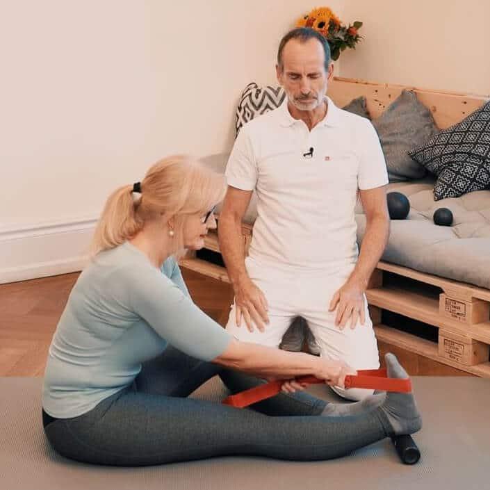 Eine Frau sitzt auf dem Boden und streckt ihr rechtes Bein aus, um dieses mithilfe einer Übungs-Schlaufe zu dehnen. Unter ihrer Ferse liegt die Mini-Faszienrolle.