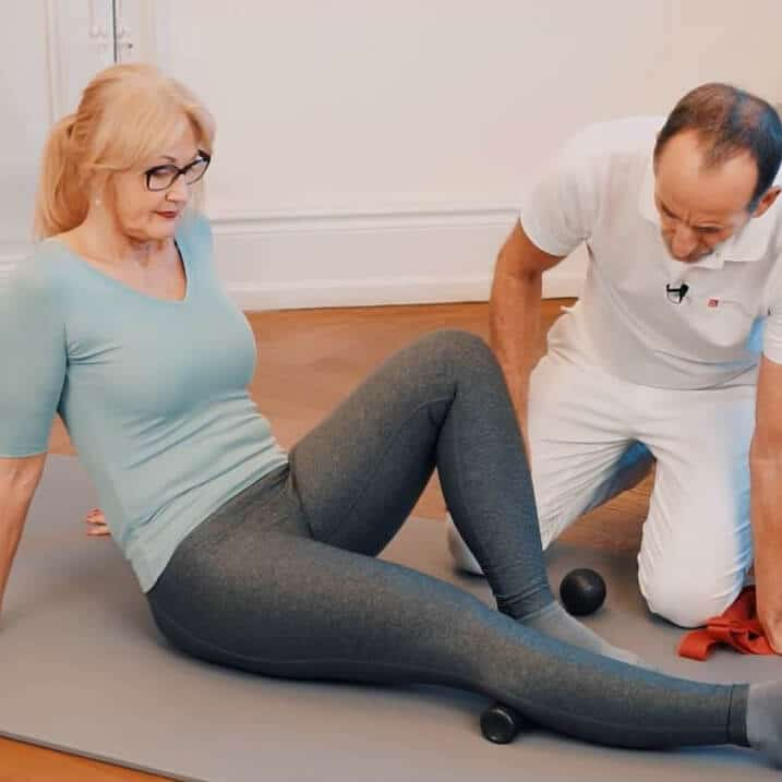 Eine Frau sitzt auf dem Boden, streckt ihr rechtes Bein von sich und rollt ihre Wade mit der Mini-Faszienrolle ab.