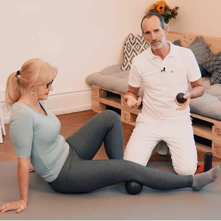 Eine Frau sitzt auf dem Boden und streckt ihr rechtes Bein aus, um ihre Kniekehle mit der Medi-Faszienkugel abzurollen und ihre Bakerzyste damit zu behandeln.