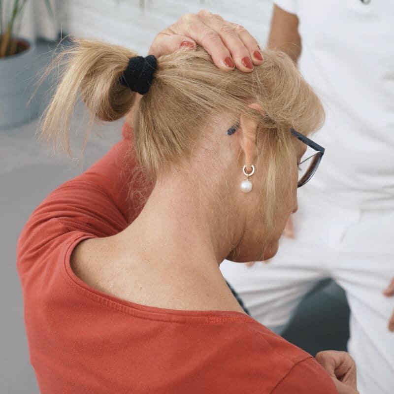 Man sieht den Nacken einer Frau, deren Kopf leicht nach rechts gedreht und Kinn runter in Richtung Brust geneigt ist. Ihre rechte Hand liegt auf ihrem Hinterkopf auf, um den Kopf nach links zu strecken. Außerdem hat sie ihre rechte Hand zu einer Faust geballt an die rechte Schulter gehoben.