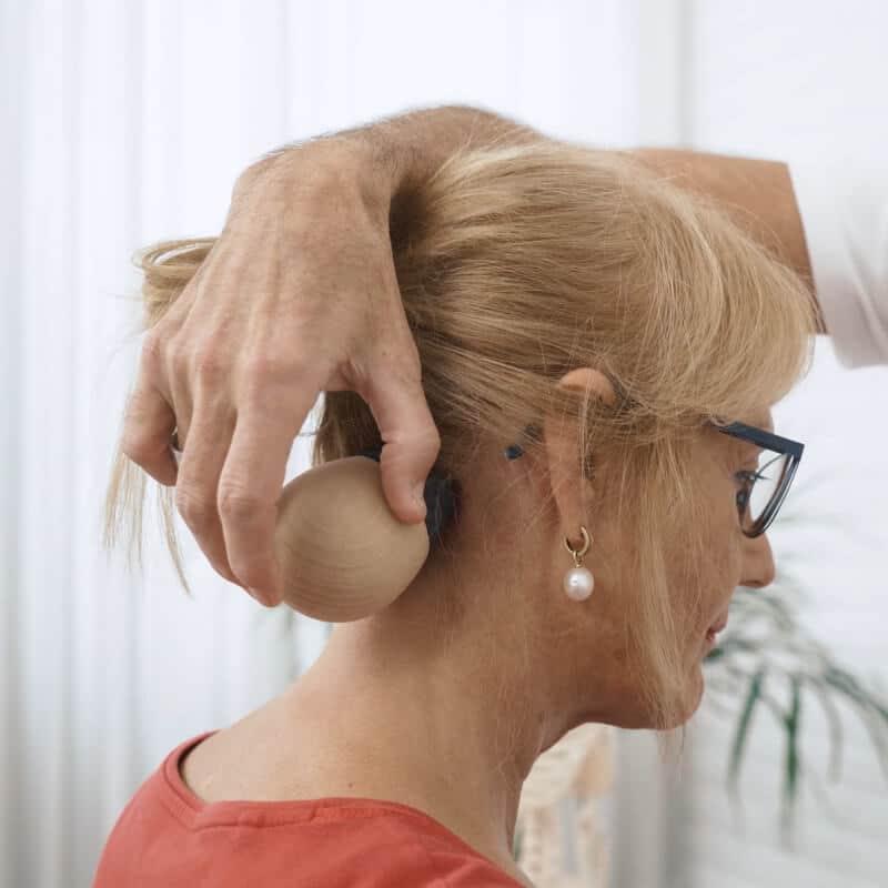 Man sieht den Hinterkopf einer Frau und wie Roland Liebscher-Bracht den Schmerzfrei-Druecker mit dem runden Griff und dem flachen Aufsatz auf eine Stelle hinter ihrem Ohr haelt.