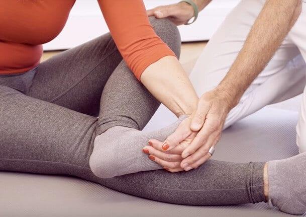 Dehnung der Fußsohle zur Behandlung einer Hammerzehe und eines Spreizfußes. Zu sehen ist, wie die Zehen nach oben gezogen werden