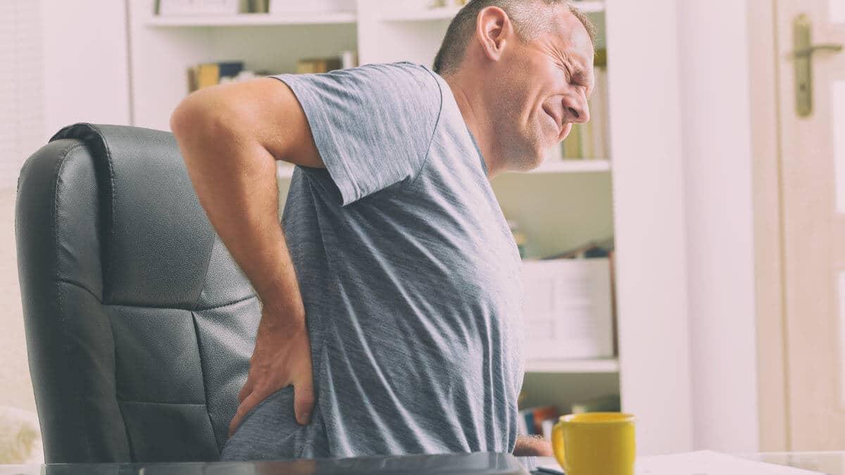 Mann sitzt auf einem Buerostuhl und haelt sich seine schmerzende Lendenwirbelsaeule