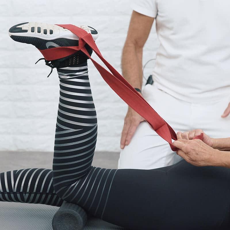 Eine Frau liegt in Bauchlage auf einer Matte und dehnt in einer Dehnungsübung mit einer Schlaufe ihre Knie und Oberschenkel, indem sie ihr Bein zum Gesäß führt.