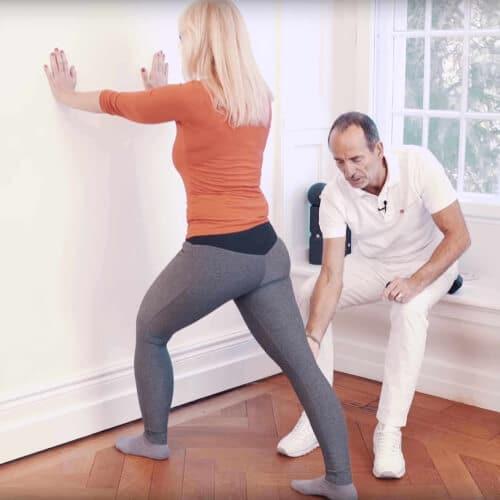 Eine Frau stuetzt sich mit ausgestreckten Armen und den Haenden an der Wand ab. Ein Bein ist nach vorne angewinkelt und das zweite nach hinten komplett ausgestreckt. Roland Liebscher-Bracht sitzt neben ihr und korrigiert ihre Bein-Position.