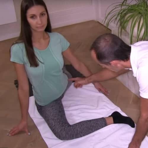 Uebung eins: Eine Frau sitzt auf dem Boden. Ihr rechts Bein liegt nach vorne in einem rechten Winkel. Das linke Bein liegt nach hinten langgestreckt aus. Roland Liebscher-Bracht zeigt auf ihre linke Leiste.