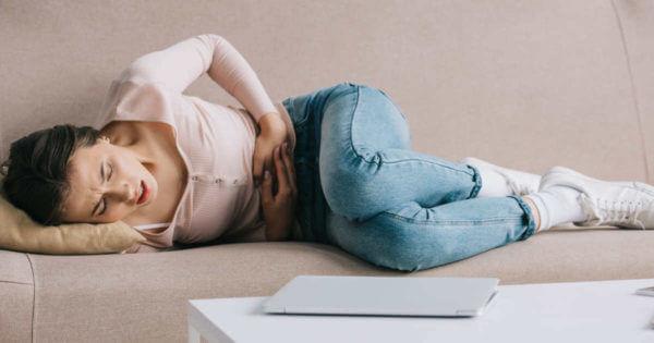 Frau liegt gekrümmt auf dem Sofa und hält sich den Bauch