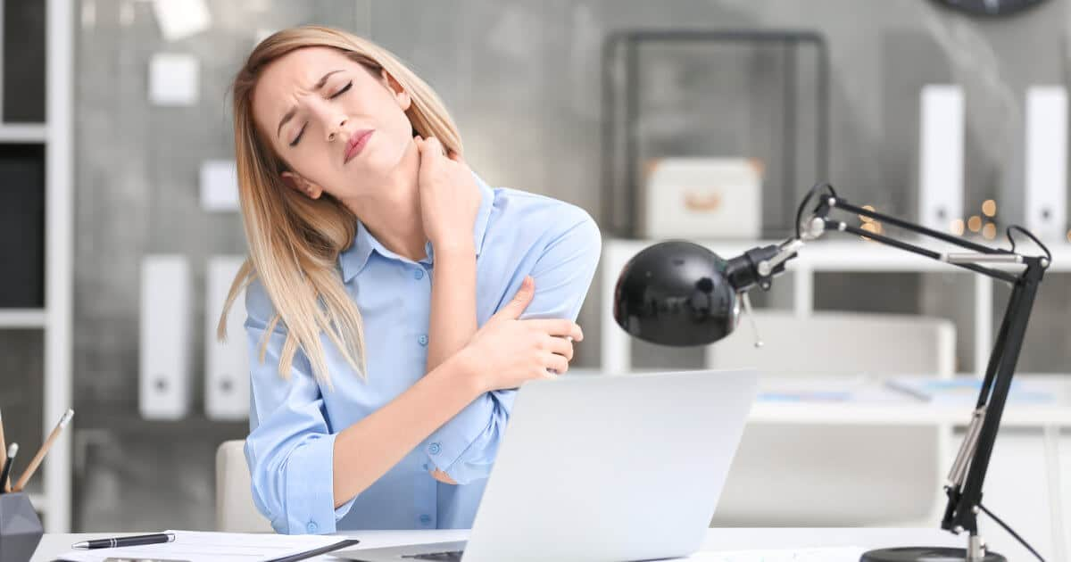 Eine junge Frau sitzt im Büro und hält sich vor Schmerzen ihren Nacken