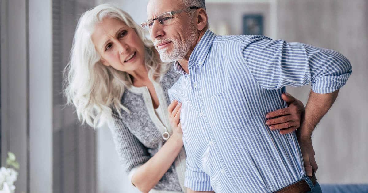 Ein aelterer Mann beugt sich vor Schmerzen nach vorne und haelt sich mit einer Hand den Ruecken fest. Eine ebenfalls aeltere Frau versucht ihn zu stuetzen und legt ihre Arme um den Oberkloerper des Mannes.