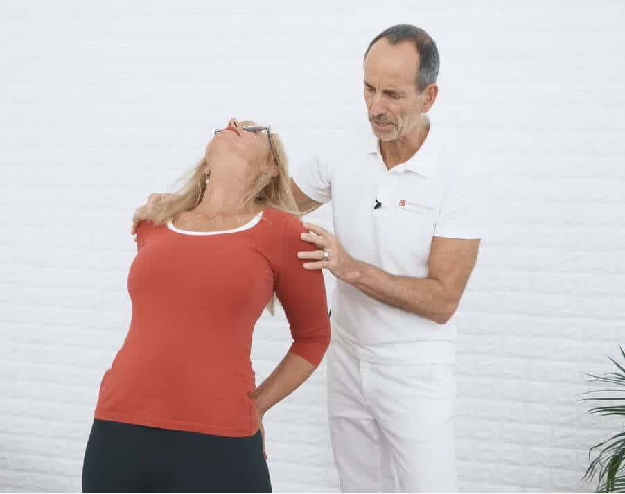 Eine Frau macht eine Übung gegen Skoliose und beugt sich dafür nach hinten.