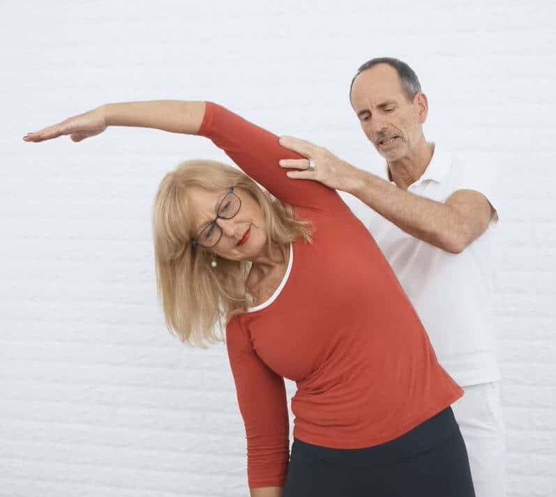 Eine Frau macht eine Skoliose Übung und hebt dafür ihren linken Arm über ihren Kopf, während sie sich nach rechts beugt.