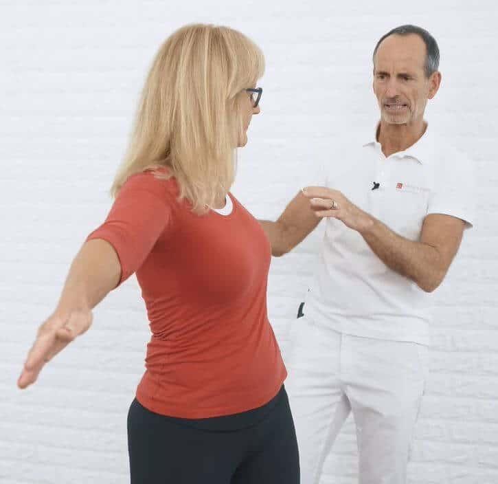Eine Frau macht eine Übung gegen Skoliose, indem sie ihre Arme ausstreckt und ihren Oberkörper nach links dreht.