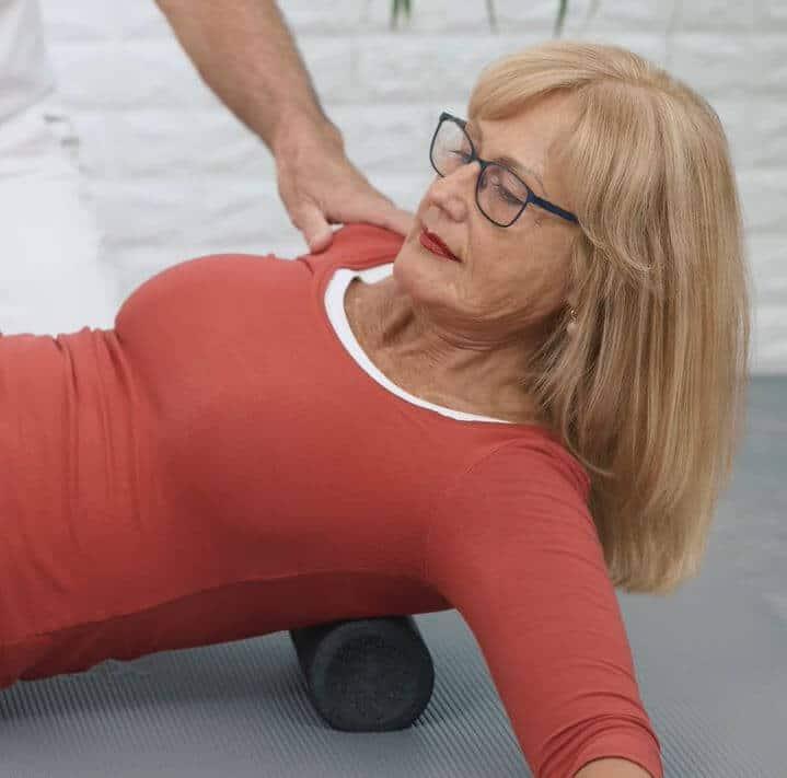 Eine Frau macht eine Übung gegen Skoliose, indem sie sich über die Medi-Faszienrolle von Liebscher & Bracht rollt.