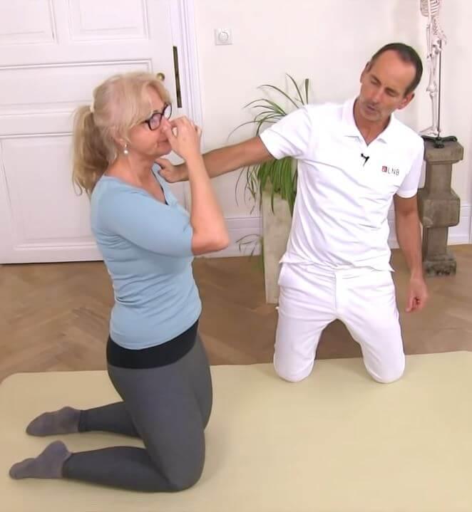 Eine Frau macht eine Atemübung gegen Rückenschmerzen im oberen Rücken, indem sie auf dem Boden kniet und sich die Nase zuhält..
