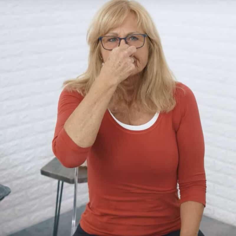 Eine Frau macht eine Atemübung gegen Sodbrennen, indem sie sich die Nase zuhält und durch Einatmungs-Versuche ein Vakuum erzeugt