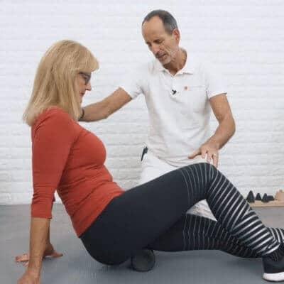 Eine Patientin mit Hüftblockade rollt ihre Gesäßmuskulatur mithilfe der Medi-Rolle ab. Schmerzspezialist Roland Liebscher-Bracht leitet sie an.