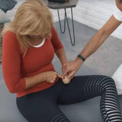 Eine Patientin mit Hüftblockade führt eine Light-Osteopressur am Hüftbeuger durch. Sie sitzt auf einer Matte und drückt mithilfe des Schmerzfrei-Drückers einen Knochenpunkt auf Höhe des linken, mittleren Oberschenkels
